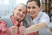 stock photo of lonely woman  - Senior woman and female nurse are showing thumbs up - JPG