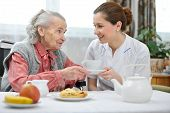 stock photo of granddaughters  - Senior woman eats lunch at retirement home - JPG