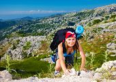 Cute teen girl clambering on the top of mountain, extreme adventure, summer traveling, freedom conce