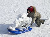 foto of ruddy-faced  - Funny little boy with sledge outdoors in winter - JPG