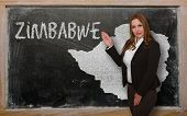 Teacher Showing Map Of Zimbabwe On Blackboard