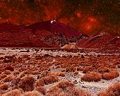 An alien landscape with a large volcano and arid red landscape with red nebula in the background. El