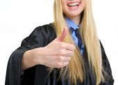 Closeup auf junge Frau In Graduation Kleid Showing Thumbs Up