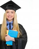 Happy Young Woman In Graduation Gown With Books