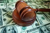 image of court hammer  - closeup of a legal gavel on US cash - JPG