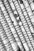 stock photo of current affairs  - A black and white background of English language newspapers stacked and folded in a diagonal position and viewed in close up - JPG