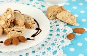 Aromatic cookies cantuccini on plate with cup of coffee on blue tablecloth close-up