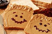 Making peanut butter sandwiches with personality! Fun smiley faces drawn on with jam. Creamy peanut