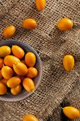 pic of kumquat  - Fresh Organic Raw Kumquats Citrus Fruit against a background - JPG