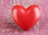 Decorative red heart on color wooden background