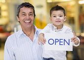 image of daddy  - Business owner and son holding an open sign - JPG