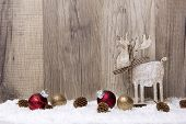 stock photo of cone  - christmas decoration with wood background snow elk christmas baubles gold and red and pine cones - JPG