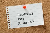 picture of soliciting  - Looking for a Date typed on a piece of lined paper and pinned to a cork notice board - JPG