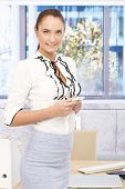 Portrait of pretty businesswoman standing in bright office with mobile phone handheld, smiling.