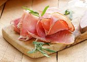 parma ham (jamon) sliced ??on a wooden board