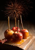 Group of toffee apples on rustic wooden board with fireworks in the background