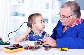 Grandfather Teaching Grandchild Working With Soldering Iron