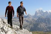 stock photo of mans-best-friend  - Young men hiking in the mountains Alps Italy