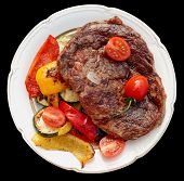 Kobe beef ribeye steak with grilled vegetables on old table isolated on black