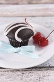 Chocolate Cupcake With Festive Red Maraschino Cherries On Pale Aqua Blue Shabby Chic Table.