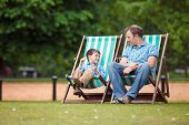 Happy father and son having rest in city park