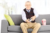 Senior man seated on a couch playing video games at home