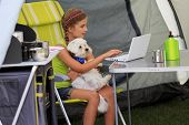 Summer camp - young girl with dog playing in the tent