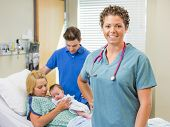 Portrait of successful nurse standing with couple and newborn baby in background at hospital