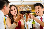 Two Asian Chinese Couples or friends or business people toasting during dinner or lunch in a elegant