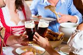 Young people in traditional Bavarian Tracht eating with sausages in restaurant or pub lunch or dinne