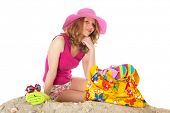 woman sitting at the beach with pink hat in studio isolated over white background