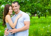 Young couple embracing near blossomed tree in the park. Concept of love and stable relations