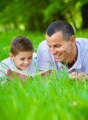 Father and son read book lying on green grass in park. Concept of happy family relations and carefree leisure time