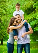 Happy family of three. Father keeps son on shoulders. Concept of happy family relations and carefree