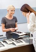 image of jewel-case  - Shop assistant helps lady to choose jewelry at jeweler - JPG