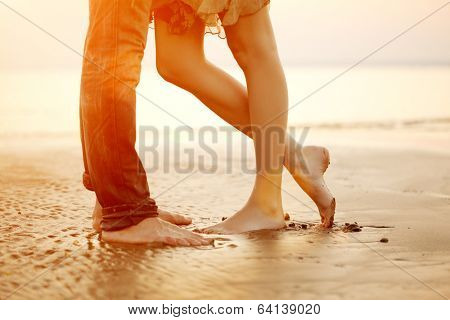A young  loving  couple hugging and kissing on the beach at sunset. Two lovers, man and woman barefo poster