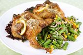 Roasted quails with vegetables on plate, on wooden background
