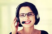 Closeup of attractive customer support representative smiling with headset on white background