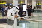 DOHA, QATAR - FEBRUARY 18, 2014: Muslim man wearing traditional clothes holding Kuran and looking at cell phone at Doha International Airport, the only commercial airport in Qatar.