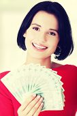 stock photo of zloty  - Cheerful young lady holding cash  - JPG
