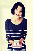 Happy woman holding euros bills and house model - real estate loan concept