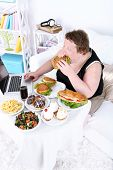 Fat man has a big lunch and playing games on laptop, on home interior background