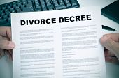 closeup of man hands holding a divorce decree on a desk