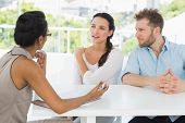 pic of therapist  - Therapist talking with couple sitting at desk in therapists office - JPG