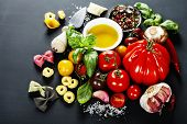 Italian ingredients - pasta, vegetables, spices, cheese - on dark background