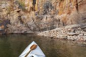 picture of horsetooth reservoir  - canoe bow with a paddle on Horsetooth Reservoir with a high sandstone cliff - JPG
