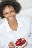 A beautiful mixed race African American girl or young woman looking happy and eating fruit salad in