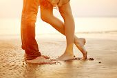 stock photo of lovers  - A young  loving  couple hugging and kissing on the beach at sunset - JPG