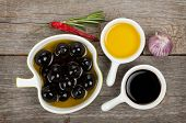 Olives, olive oil and vinegar with spices over wooden table background