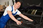 Mechanic In Garage Repairing Car